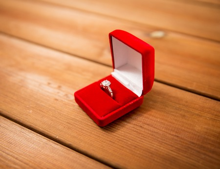 diamond ring: proposal, engagement, valentines day and holidays concept - close up of red gift box with diamond engagement ring on wood