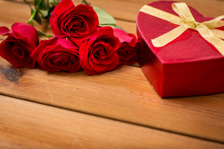 attentions: love, date, romance, valentines day and holidays concept - close up of heart shaped gift box and red roses on wooden table