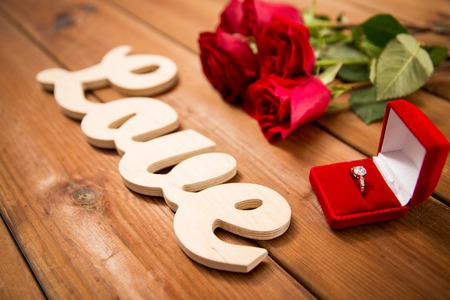 proposal, romance, valentines day and holidays concept - close up of gift box with diamond engagement ring, red roses and word love on wood Stock Photo