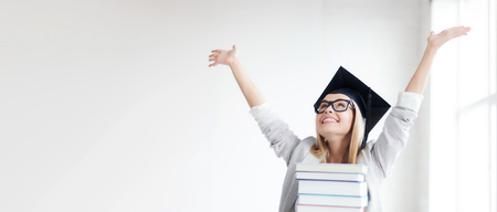 successful woman: happy student in graduation cap with stack of books Stock Photo