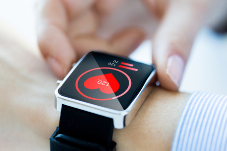 health technology: technology, health care and people concept - close up of woman hands checking pulse by smartwatch with heart icon on screen