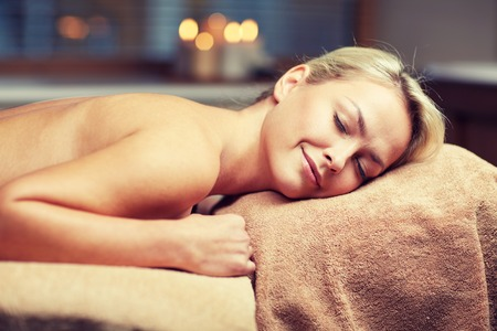 massage table: people, beauty, spa, healthy lifestyle and relaxation concept - beautiful young woman lying on massage table in spa