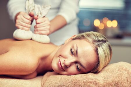 spa woman: people, beauty, spa, healthy lifestyle and relaxation concept - close up of beautiful young woman lying and having herbal bag massage in spa Stock Photo