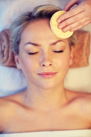 massagist: people, beauty, spa, healthy lifestyle and relaxation concept - close up of beautiful young woman lying with closed eyes and having face massage with sponge in spa Stock Photo