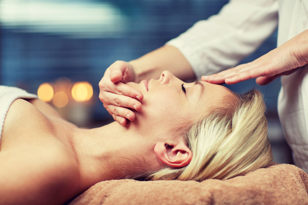 people, beauty, spa, healthy lifestyle and relaxation concept - close up of beautiful young woman lying with closed eyes and having face or head massage in spa Stockfoto
