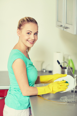 dish: people, housework and housekeeping concept - happy woman in protective gloves washing dishes at home kitchen