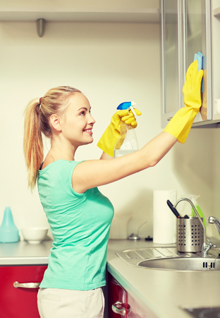 cleanser: people, housework and housekeeping concept - happy woman in protective gloves cleaning cabinet with rag and cleanser at home kitchen