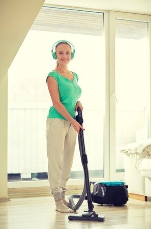 housecleaning: people, housework, technology and housekeeping concept - happy woman in headphones with vacuum cleaner cleaning floor at home