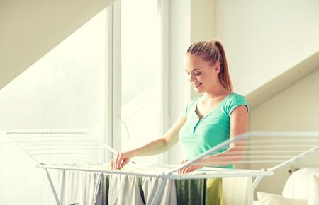 les gens, le ménage, la lessive et le concept de ménage - femme heureuse suspendre les vêtements sur les sèche à la maison Banque d'images