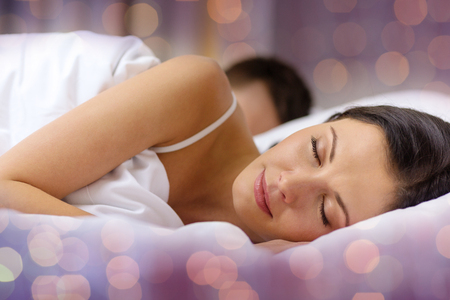 enamorados en la cama: la gente, el descanso, las relaciones y el concepto de vacaciones - feliz pareja durmiendo en la cama más de fondo de las luces