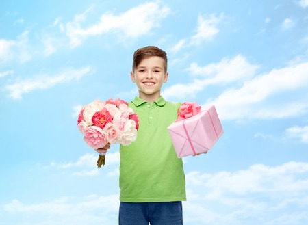 pre teen boys: childhood, holidays, presents and people concept - happy boy holding flower bunch and gift box over blue sky and clouds background Stock Photo