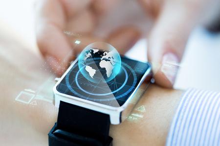 negocios, tecnología, comunicación, conexión y el concepto de la gente - cerca de holograma manos de la mujer globo en SmartWatch