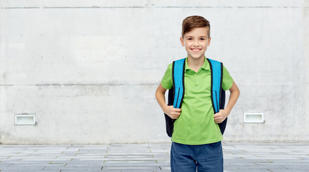 young boys: childhood, school, education and people concept - happy smiling student boy with school bag over urban street background Stock Photo