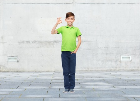 pre teen boy: childhood, fashion, advertisement and people concept - happy boy in white t-shirt and jeans showing ok hand sign over urban street background