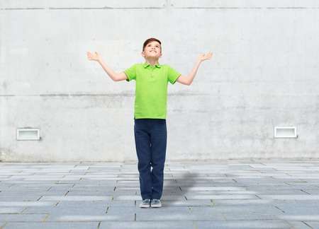 pre teen boy: childhood, achievement, gladness and people concept - happy smiling boy in green polo t-shirt raising hands and looking up over urban street background