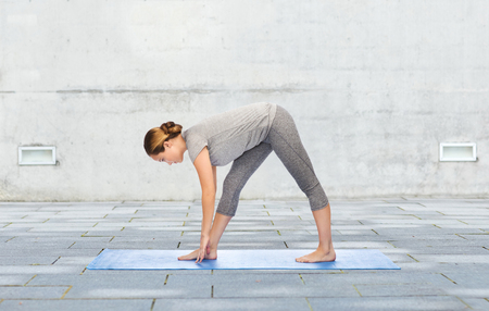 stretch: fitness, sport, people and healthy lifestyle concept - woman making yoga intense stretch pose on mat over urban street background