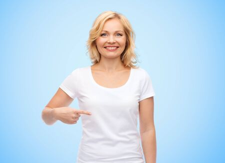PRETTY WOMEN: gesture, advertisement and people concept - smiling middle aged woman in blank white t-shirt pointing finger to herself over blue background