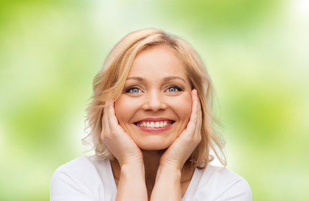 beauty, people and skincare concept - smiling middle aged woman in white shirt touching face over green natural background Standard-Bild