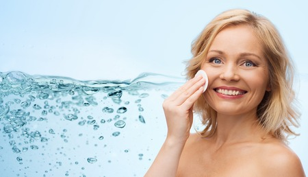 removing make up: beauty, people and skincare concept - happy middle aged woman cleaning face and removing make up with cotton pad over water splash with air bubbles background
