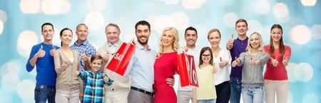 familias felices: gesto, venta, compras y concepto de la gente - grupo de la sonrisa de hombre, mujer y niño pulgares a aparecer durante las vacaciones luces de fondo azul