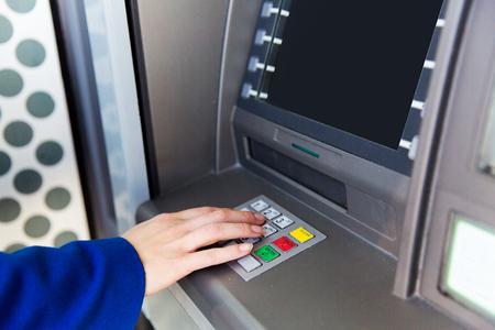 financiën, technologie, geld en mensen concept - close-up van de hand invoeren van de pincode bij geldautomaat