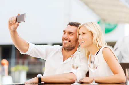 couple outdoor: love, date, technology, people and relations concept - smiling happy couple taking selfie with smartphone at city street cafe