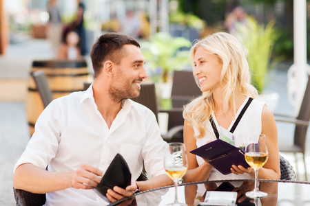 paying: date, people, payment and financial independence concept - happy couple with cash money in wallets and wine glasses paying bill at restaurant