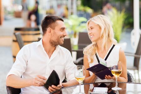 pagando: fecha, la gente, el pago y el concepto de independencia financiera - pareja feliz con dinero en efectivo en las carteras y las copas de vino que pagan la factura en el restaurante