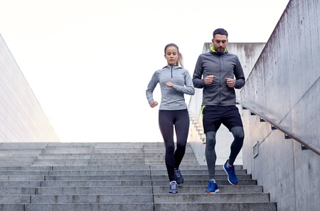 warm up exercise: fitness, sport, exercising, people and lifestyle concept - couple walking downstairs on stadium Stock Photo