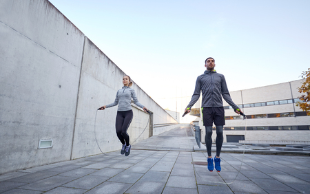 fitness, sport, people, exercising and lifestyle concept - man and woman skipping with jump rope outdoors Reklamní fotografie