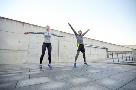jumping: fitness, sport, people, exercising and lifestyle concept - happy man and woman jumping outdoors Stock Photo