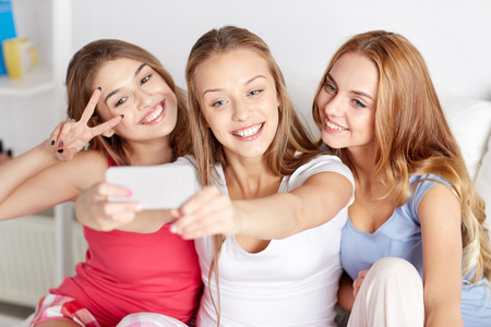 pajama party: friendship, people, pajama party and technology concept - happy friends or teenage girls with smartphone taking selfie at home