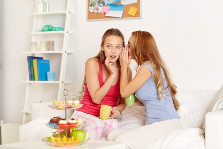 scandalous: friendship, people, pajama party and communication concept - happy friends or teenage girls drinking tea with sweets and gossiping at home