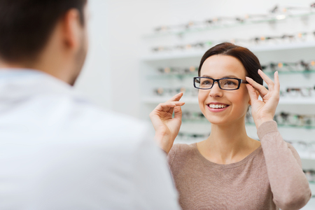 health care, people, eyesight and vision concept - happy woman with optician choosing glasses at optics store