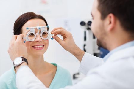 건강 관리, 의학, 사람, 시력 및 기술 개념 - 안경점 또는 광학 저장소에서 환자의 비전을 검사하는 평가판 프레임을 가진 검안사
