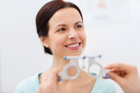 trial indoor: health care, medicine, people, eyesight and technology concept - happy woman having vision test with trial frame at eye clinic or optics store Stock Photo