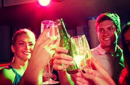 party people: party, holidays, celebration, nightlife and people concept - smiling friends clinking glasses of champagne and beer in club Stock Photo