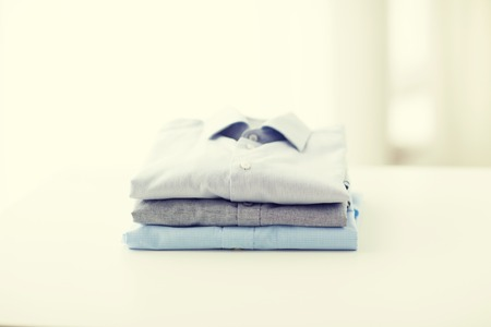 ironed: ironing, laundry, clothes, housekeeping and objects concept - close up of ironed and folded shirts on table at home Stock Photo