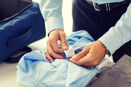 packing suitcase: business, trip, luggage and people concept - close up of businessman packing clothes into travel bag Stock Photo