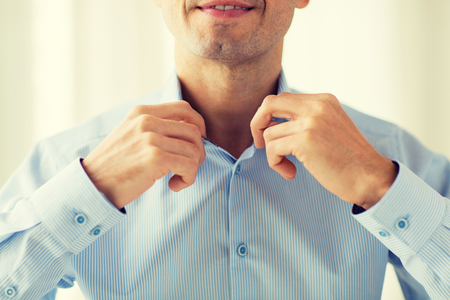 formal dressing: people, business, fashion and clothing concept - close up of smiling man dressing up and adjusting shirt collar at home