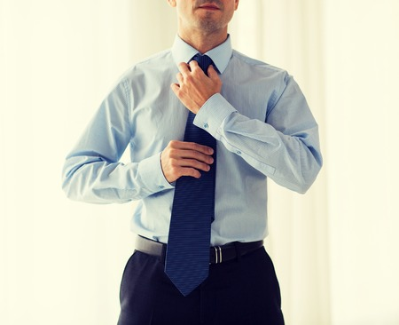 office man: people, business, fashion and clothing concept - close up of man in shirt dressing up and adjusting tie on neck at home