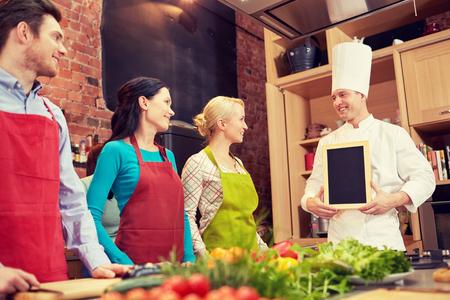 amateur: clase de cocina, culinario, comida y gente concepto - amigos felices y chef cocinar con tablero de tiza de menú en blanco en la cocina Foto de archivo