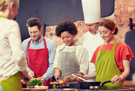 cooking: cooking class, culinary, food and people concept - happy group of friends and male chef cook cooking in kitchen Stock Photo