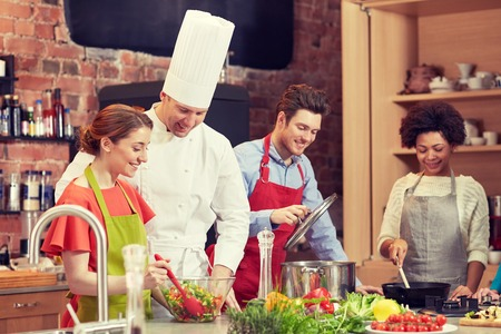 food concept: cooking class, culinary, food and people concept - happy group of friends and male chef cook cooking in kitchen Stock Photo