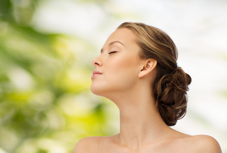 ojos verdes: la belleza, la gente y el concepto de salud - Cara de la mujer joven con los ojos cerrados y los hombros vista lateral sobre fondo verde natural