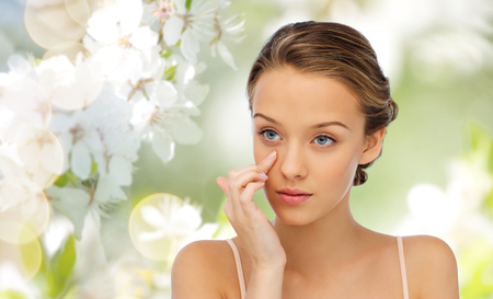 beauty, people, cosmetics, skincare and health concept - young woman applying cream to her face over cherry blossom background