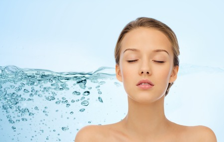beauty, people, moisturizing, skin care and health concept - young woman face with closed eyes and shoulders over water splash background