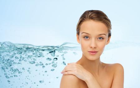 Schönheit, Menschen, Körperpflege, feuchtigkeitsspendend und Gesundheit Konzept - junge Frau Gesicht und Hand auf nackte Schulter über Wasser spritzen Hintergrund lächelnd