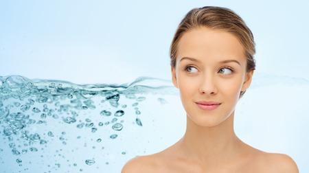 Concepto de belleza, personas, hidratación, cuidado de la piel y salud - sonriente joven cara y hombros sobre fondo de salpicaduras de agua Foto de archivo