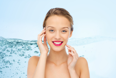 beauty, people, moisturizing, skin care and health concept - smiling young woman face with pink lipstick on lips and shoulders over water splash background